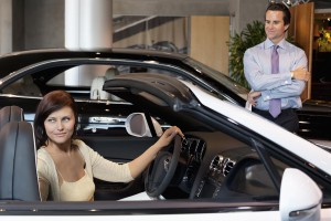 Woman having a test drive while salesperson standing besides car