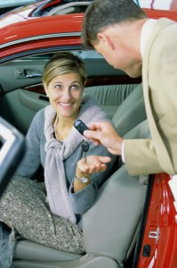 Car salesman giving the car keys to a mid adult woman