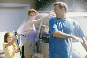 Daughter spraying water on her father with her mother washing the car